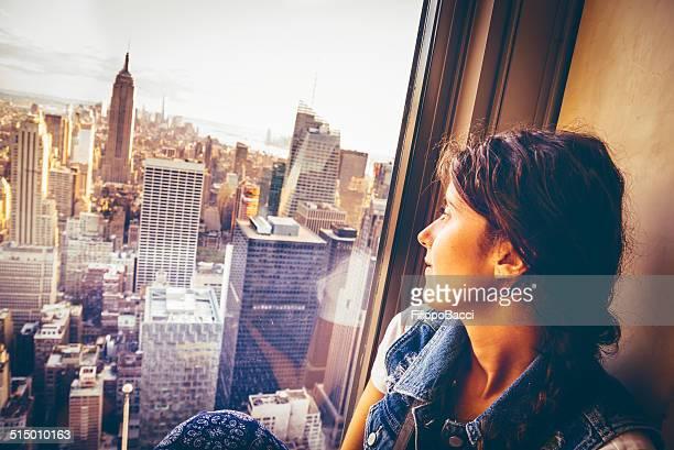 Joven mujer sentada cerca de la ventana en Nueva York