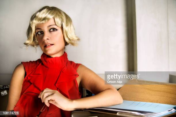 Young Woman Sitting Near File Folder Wearing Wig
