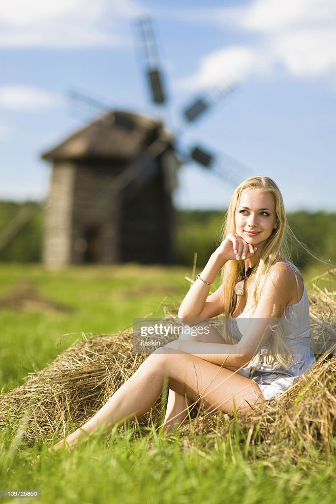Young Woman Sitting Near Windmill : Stock Photo