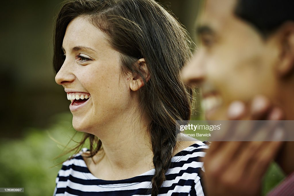 Young woman sitting next to boyfriend laughing : Stock Photo