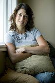 Young woman sitting, nursing cushion by window, portrait