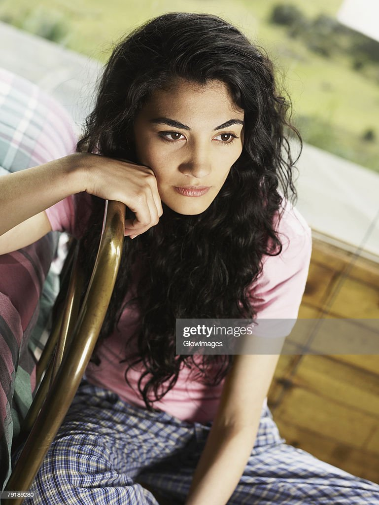 Young woman sitting on a chair and thinking : Foto de stock