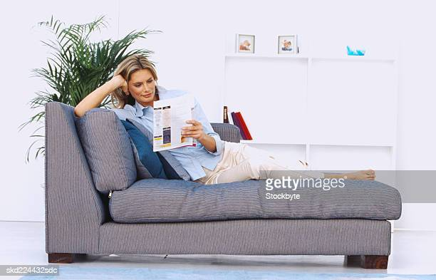 Young woman sitting on a couch reading a magazine