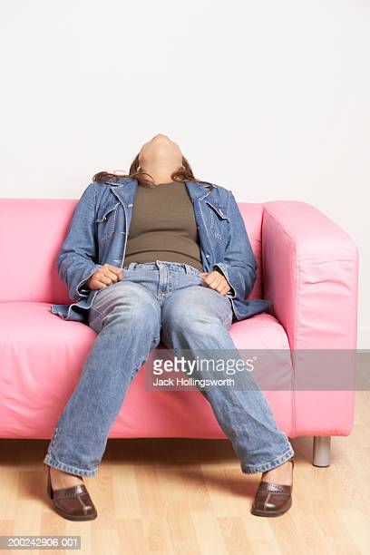 Young woman sitting on a couch with her head leaning over
