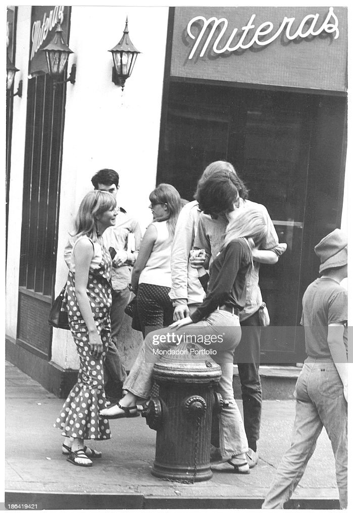 A young woman sitting on a fireplug and kissing a young man in MacDougal Street in the Greenwich Village New York September 1966
