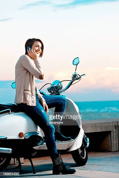 Young woman sitting on a moped bike