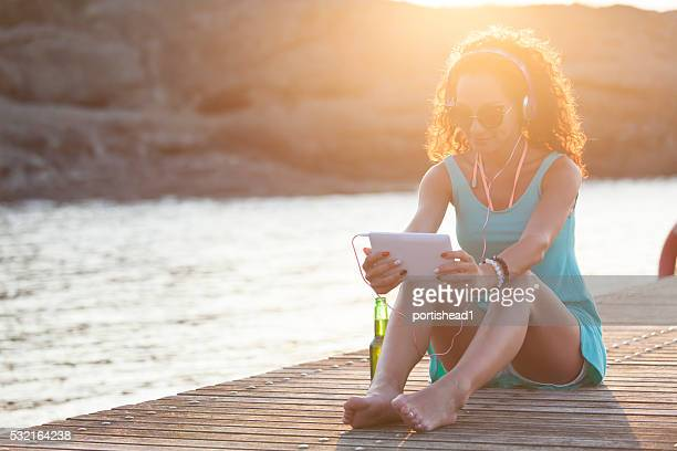 Young woman sitting on a pier and listening music