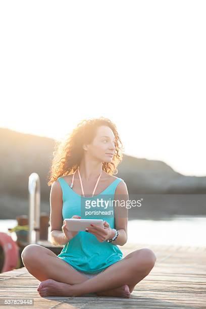 Jeune femme assis sur un quai avec tablette numérique