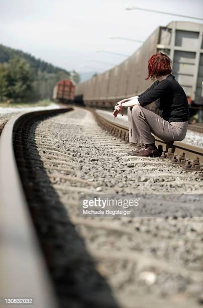 Young woman sitting on a railway track