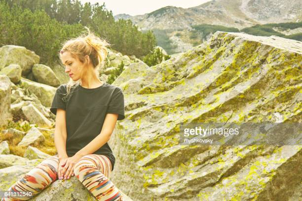 Young woman sitting on a rock in the Rila Mountains