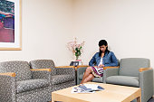 Young woman sitting on a sofa in a waiting room reading a magazine
