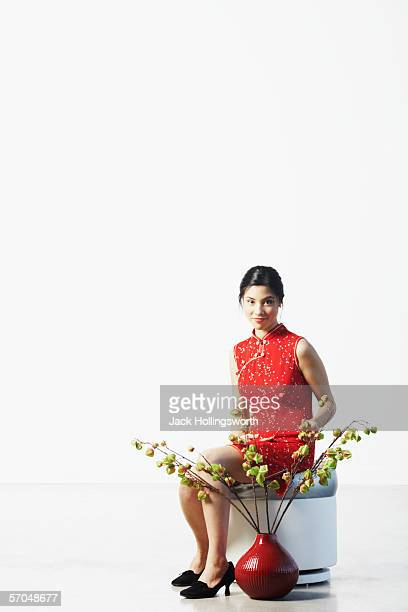 Young woman sitting on a stool touching the leaves of a potted plant
