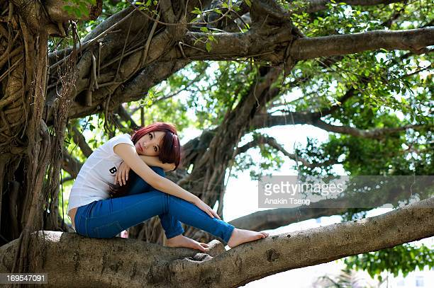 Young woman sitting on a tree branch