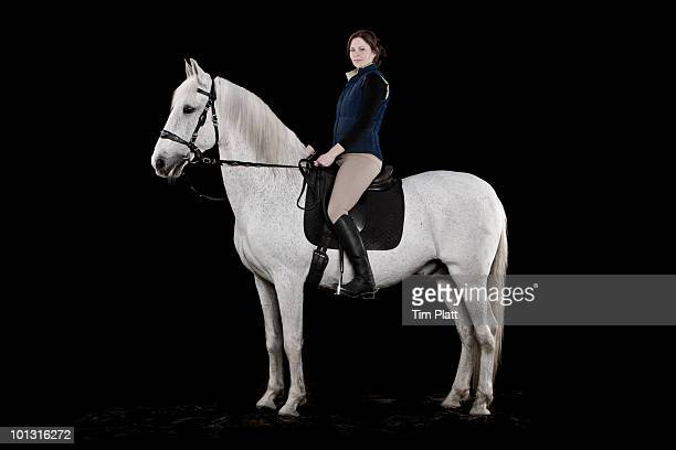 Young woman sitting on a white horse.