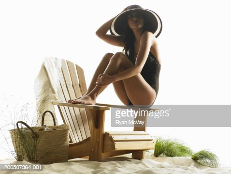 Young woman sitting on Adirondack chair in sand : Stock Photo