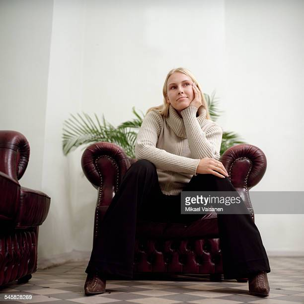 Young woman sitting on armchair, full length