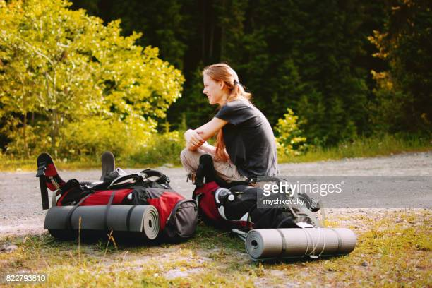 Young woman sitting on backpack