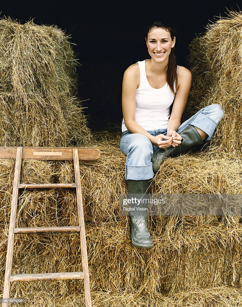 Young Woman Sitting on Bales of Hay in a Barn on a Farm : Stock Photo