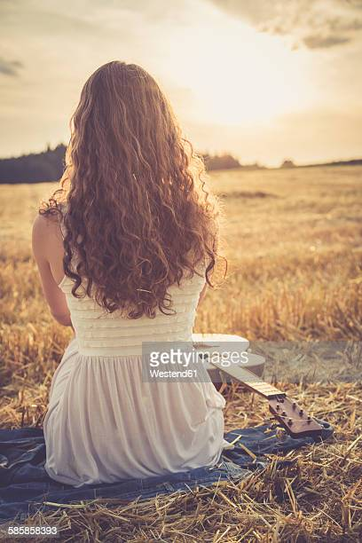 Young woman sitting on barley field in the evening