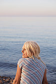 Young woman sitting on beach, back view