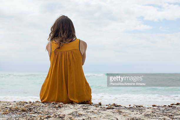 Young woman sitting on beach looking at view, rear view