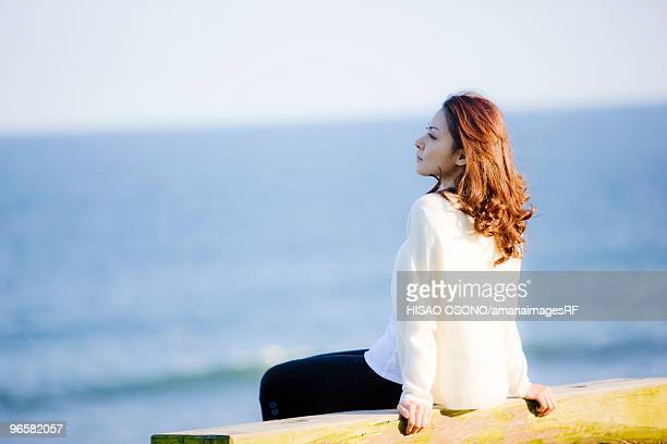 Young woman sitting on beach, looking away