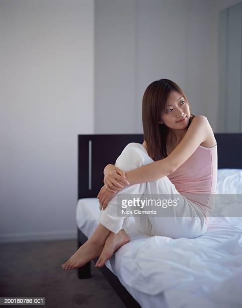 Young woman sitting on bed, smiling