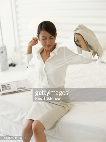 Young woman sitting on bed, stretching arms, eyes closed