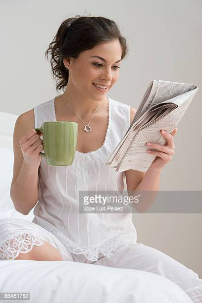 Young woman sitting on bed with coffee reading new