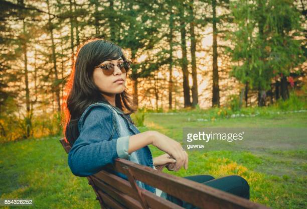 Young woman sitting on bench in park.