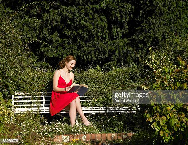 Young woman sitting on bench reading book.