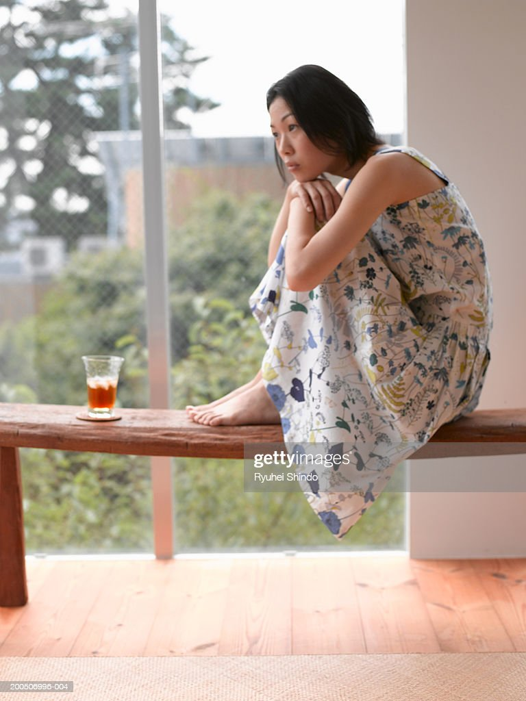 Young woman sitting on bench with beverage, side view : Stock Photo