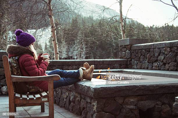 Young woman sitting on bench with fire pit, Girdwood, Anchorage, Alaska