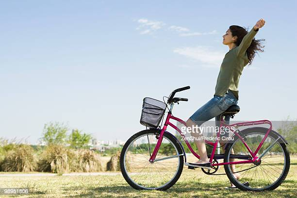 Young woman sitting on bicycle with arms out and eyes closed