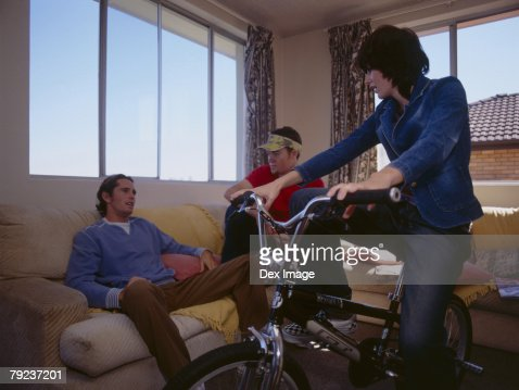 Young woman sitting on bike, while friends gather on sofa : Stock Photo