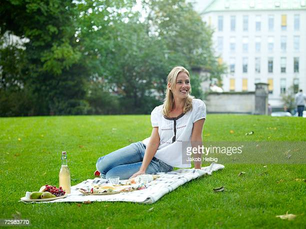Young woman sitting on blanket with picnic in  park