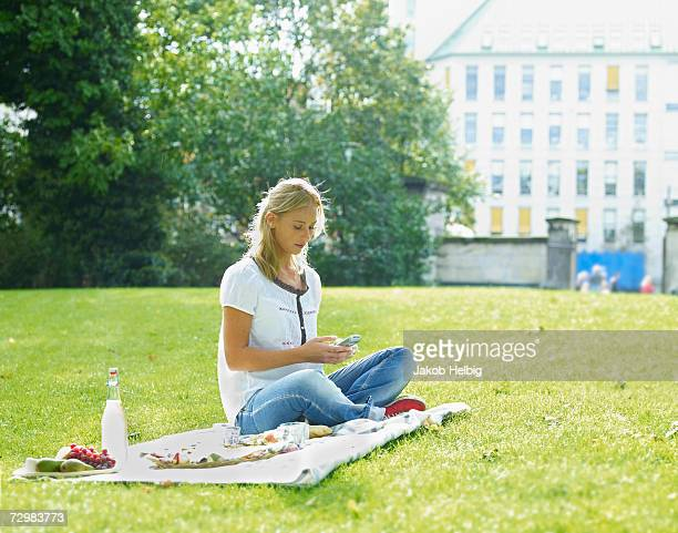 Young woman sitting on blanket with picnic in park, using mobile phone