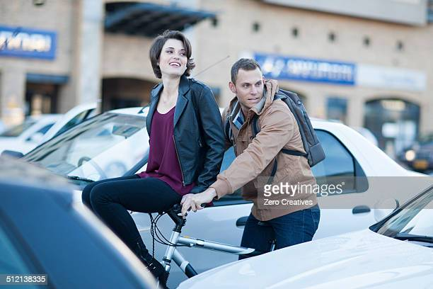 Young woman sitting on boyfriend's bicycle handlebar moving through city traffic jam