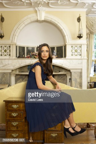 Young woman sitting on cabinet, portrait : Bildbanksbilder