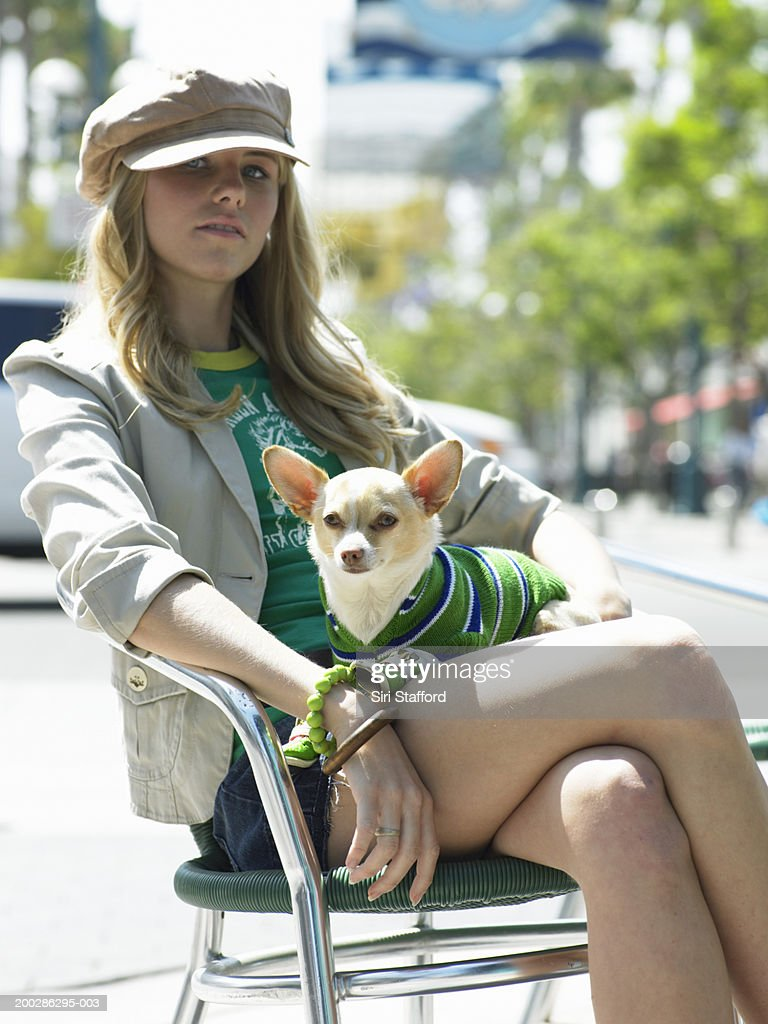 Young woman sitting on chair, dog in lap : Stock Photo