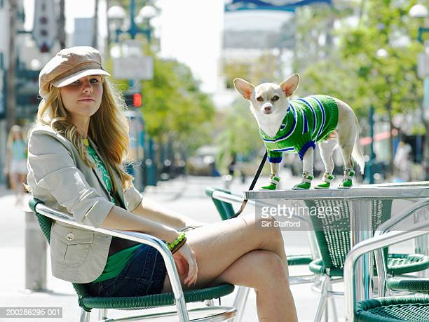 Young woman sitting on chair, dog on table