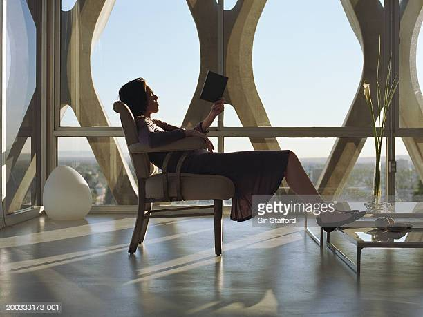 Young woman sitting on chair, feet on coffee table