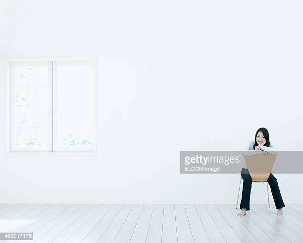 Young Woman Sitting On Chair In  Empty Room