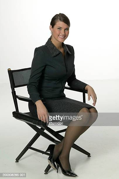 Young woman sitting on chair, posing in studio, portrait