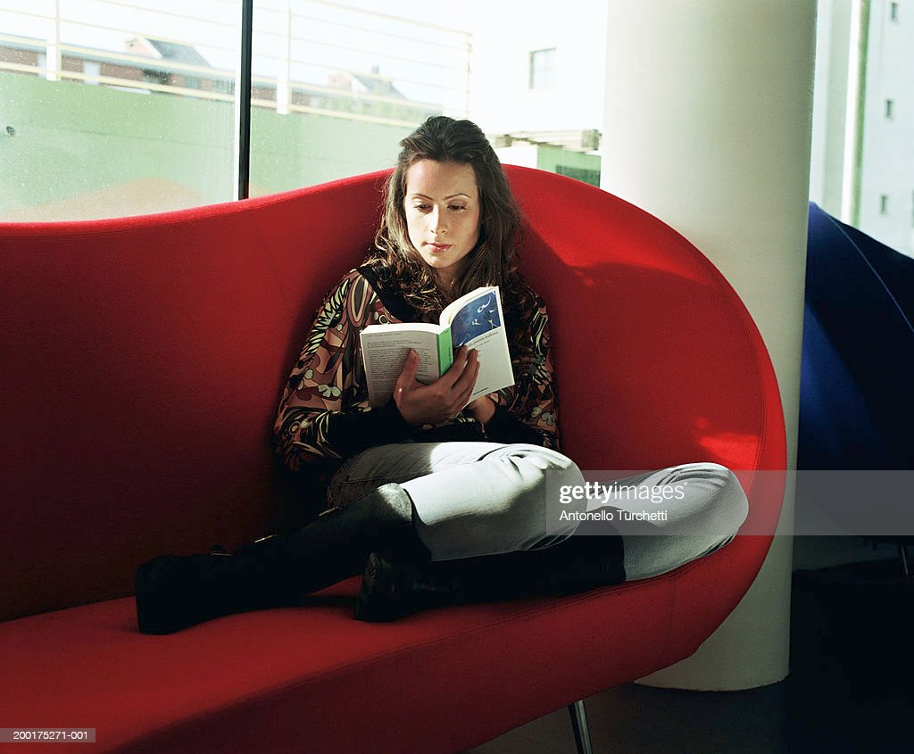 Young woman sitting on chair, reading book