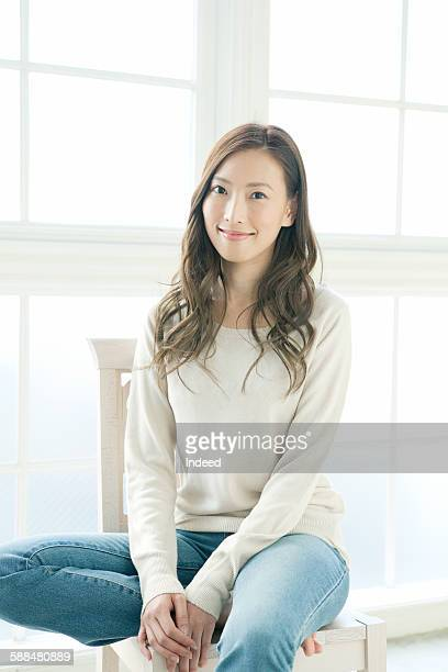 Young woman sitting on chair, smiling