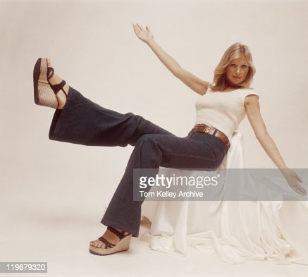 Young woman sitting on chair with arms outstretched, portrait
