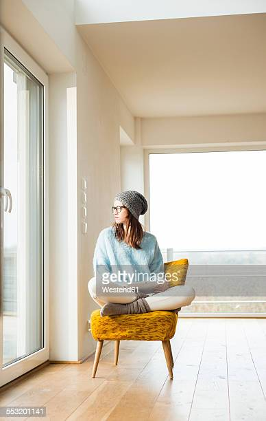 Young woman sitting on chair with digital tablet