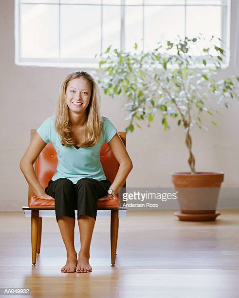 Young woman sitting on chair, with plant in background, portrait