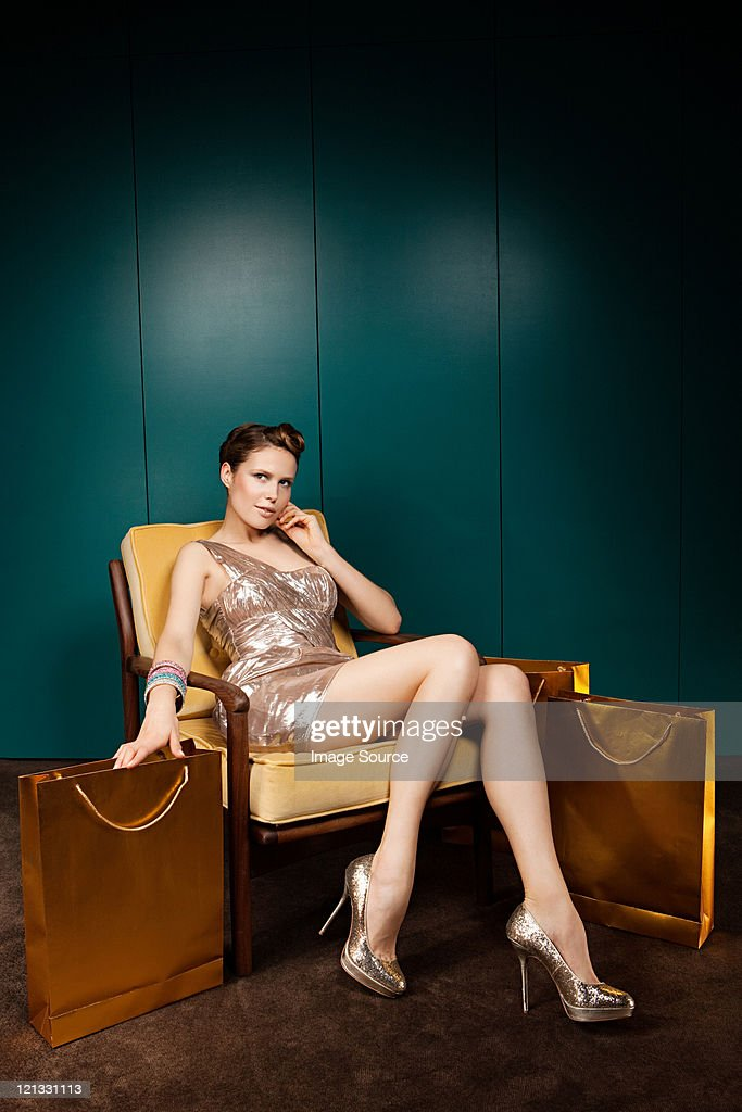 Young woman sitting on chair with shopping bags : Stock Photo